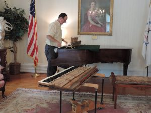 Repairman at work, restoring the Steinway.